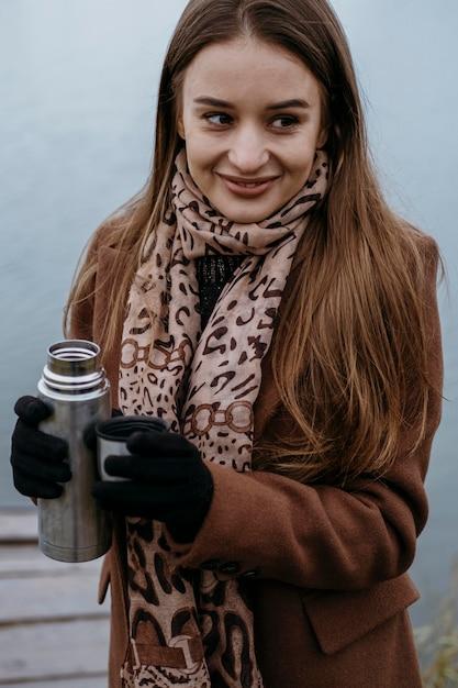 Buźka Kobieta Z Gorącym Napojem Nad Jeziorem Premium Zdjęcia