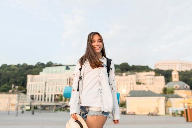 Buźka Kobieta Z Plecakiem I Kapeluszem Pozowanie Podczas Podróży Darmowe Zdjęcia