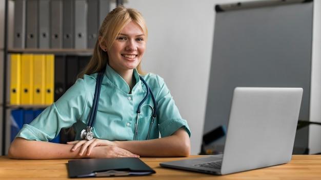 Buźka Pielęgniarka W Biurze Ze Stetoskopem I Laptopem Darmowe Zdjęcia