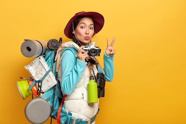 Całkiem Aktywny Backpacker Wykonuje Gest Zwycięstwa, Ma Zaokrąglone Usta, Trzyma Aparat Retro, Stoi Z Torbą Podróżną, Robi Zdjęcia Podczas Podróży, Odizolowany Na żółtym Tle Darmowe Zdjęcia