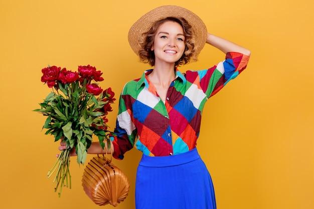 Całkiem Europejskiej Kobiety W Niebieskiej Sukience Z Bukietem Kwiatów Na żółtym Tle. Słomiany Kapelusz. Letni Nastrój. Darmowe Zdjęcia