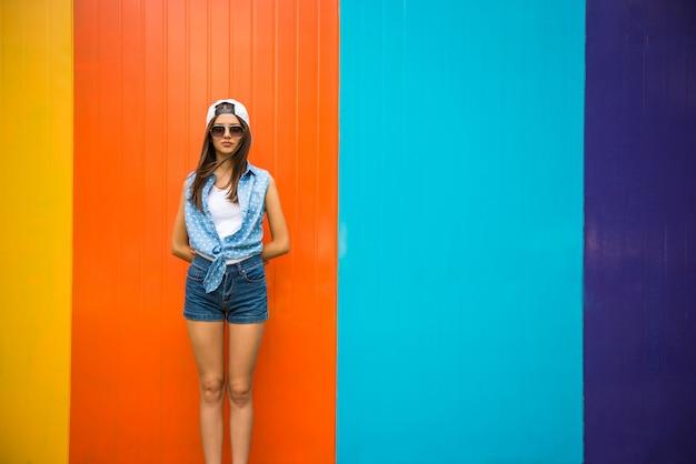 Całkiem fajna dziewczyna w okularach przeciwsłonecznych i czapce stojącej przed. Premium Zdjęcia