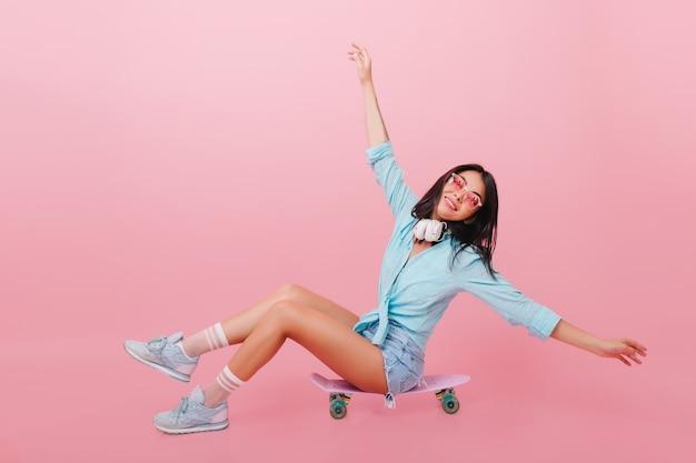 Całkiem Hiszpanin Kobieta Z Brązową Skórą Macha Rękami Siedząc Na Longboard. Zainspirowana Latynoska Dziewczyna W Okularach Przeciwsłonecznych Pozująca Na Deskorolce Darmowe Zdjęcia