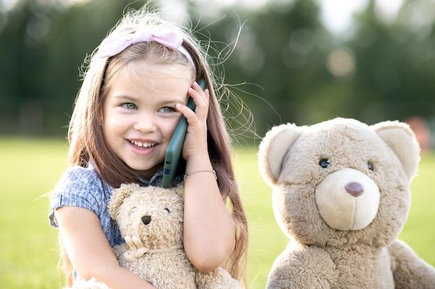 Całkiem Mała Dziewczynka Dziecko Rozmawia Przez Telefon Komórkowy Uśmiecha Się Szczęśliwie Na Zewnątrz W Lecie. Premium Zdjęcia