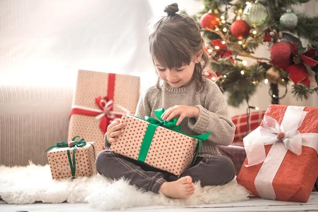 Całkiem Mała Dziewczynka Trzyma Pudełko I Uśmiecha Się, Siedząc Na łóżku W Swoim Pokoju W Domu Darmowe Zdjęcia