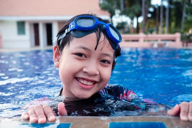 Całkiem Mała Dziewczynka W Basenie Z Uśmiechem I Szczęśliwy W Okresie Letnim Premium Zdjęcia