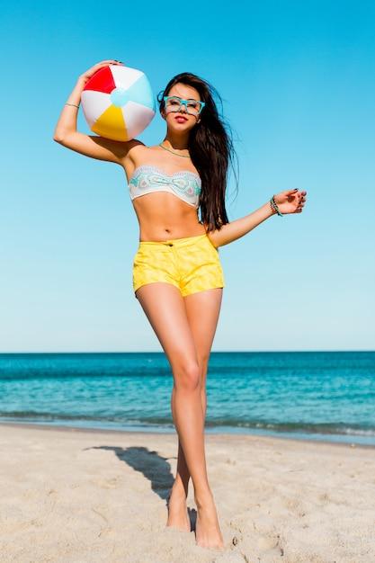 Całkiem Sexy Tan Sportive Kobieta Gra W Piłkę Na Plaży Latem. Ubrana W żółte Koszule, Kolorowy Top I Fajne Okulary. Darmowe Zdjęcia