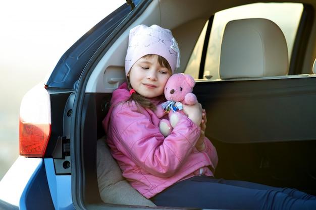 Całkiem Szczęśliwe Dziecko Dziewczyna Bawi Się Z Różowym Misiem Zabawki, Siedząc W Bagażniku Samochodu. Premium Zdjęcia