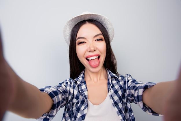 Całkiem Urocza Dziewczyna W Ubranie I Kapelusz Robi Selfie Premium Zdjęcia