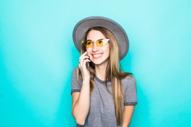 Całkiem Uśmiechnięta Młoda Modelka W T-shirt Moda, Kapelusz I Okulary Transperent Rozmawia Przez Telefon Na Białym Tle Na Zielonym Tle Darmowe Zdjęcia