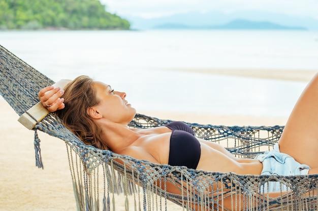 Całkiem Wesoła Młoda Dziewczyna Leżąc W Hamaku Na Plaży I Uśmiechając Się W Czarnym Bikini I Okularach Przeciwsłonecznych Premium Zdjęcia