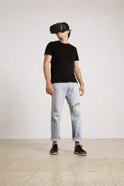 Całościowy Portret Młodego Mężczyzny W Goglach Vr, Czarnej Koszulce Bez Etykiety I Niebieskich Podartych Dżinsach Rozglądający Się Po Pokoju Z Białymi ścianami I Jasną Drewnianą Podłogą Darmowe Zdjęcia
