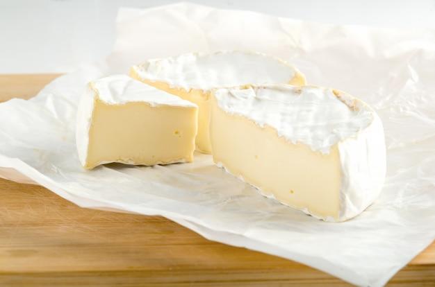 Camembert Z Kawałkiem Na Białym Papierze Pakowym Premium Zdjęcia