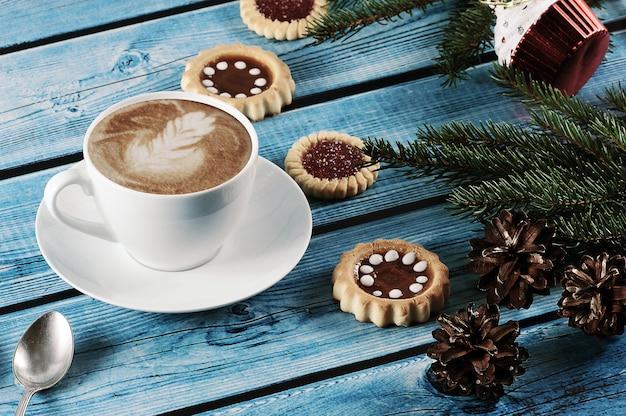 Cappuccino na bożenarodzeniowym tle z jedlinowym drzewem, rożkami, ciastkami Premium Zdjęcia