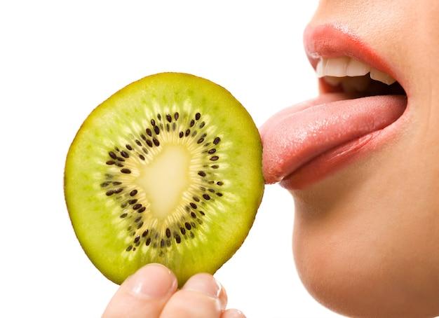 Caucasion Biała Kobieta Trzyma I Lizanie Kawałek Kiwi Premium Zdjęcia