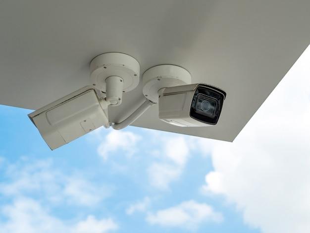 Cctv Jest Zainstalowany Pod Balkonem Budynku Na Tle Błękitnego Nieba. Cctv Do Monitorowania Bezpieczeństwa. Premium Zdjęcia