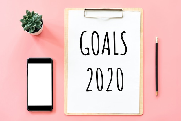 Cele 2020 i artykuły papiernicze z pustym schowkiem i smartfonem Premium Zdjęcia