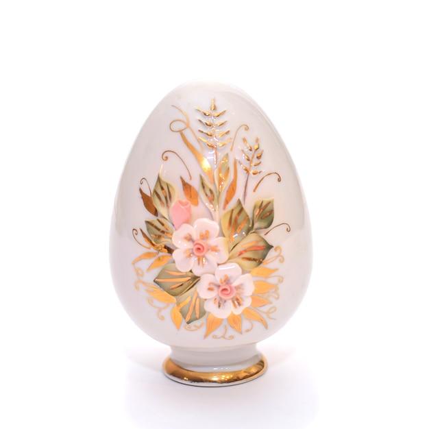 Ceramiczne Porcelanowe Ozdobne Jajko Z Malowanymi Kwiatami Na Stojaku Na Prezenty Wielkanocne, Na Białym Tle Odizolowane Premium Zdjęcia