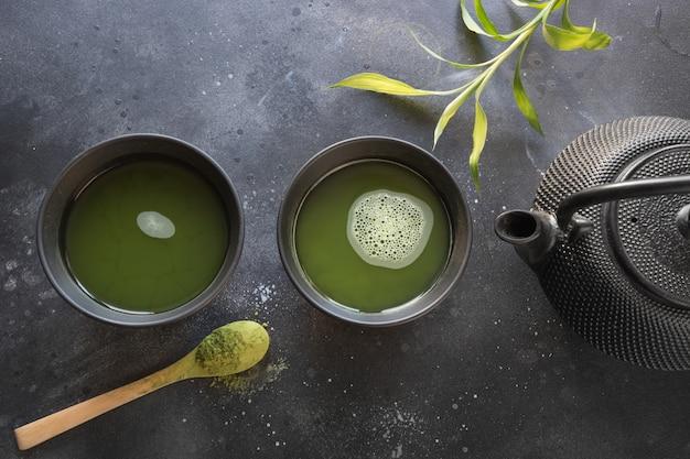 Ceremonia zielona herbata matcha i trzepaczka bambusowa na czarnym stole. widok z góry. Premium Zdjęcia