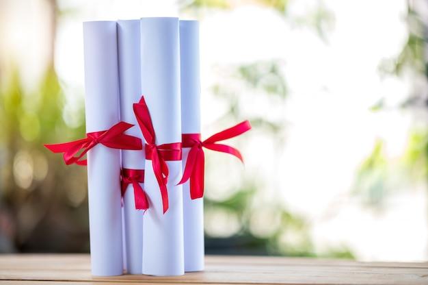 Certyfikat Absolwenci Zawiązali Czerwoną Wstążkę Na Drewnianej Podłodze. Premium Zdjęcia