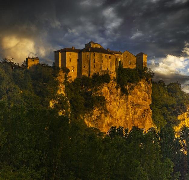 Chateau De Bruniquel Otoczony Zielenią I Skałami Pod Zachmurzonym Niebem Podczas Zachodu Słońca We Francji Darmowe Zdjęcia
