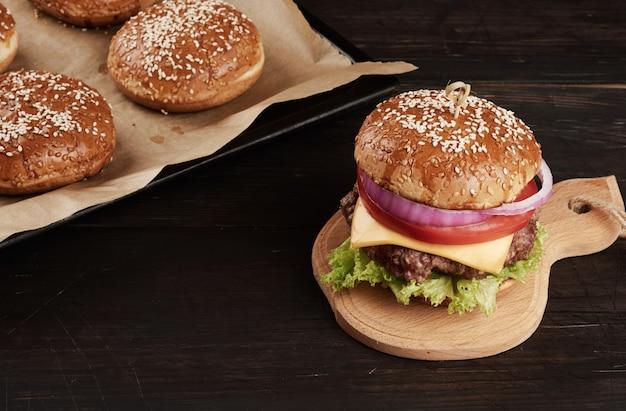 Cheeseburger Z Pomidorami, Kotletem Z Grilla I Bułką Sezamową Na Starej Drewnianej Desce Do Krojenia, Brązowa Przestrzeń. Fast Food, Widok Z Góry Premium Zdjęcia