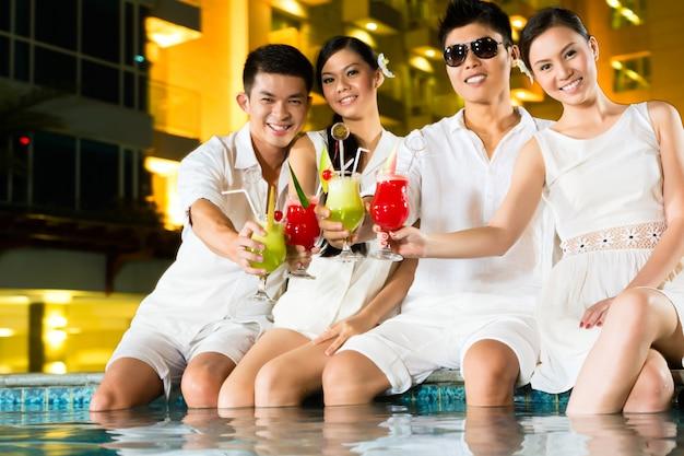 Chińskie pary pijące koktajle w hotelowym barze przy basenie Premium Zdjęcia