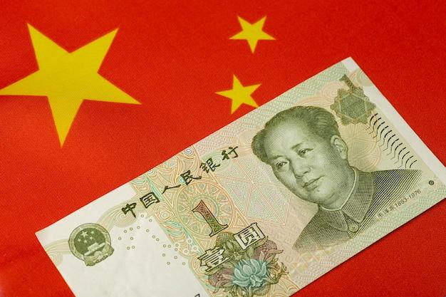 Chińskiego Juana Na Tle Chińskiej Flagi. Jeden Juan. Chińska Waluta I Koncepcja Gospodarki Premium Zdjęcia