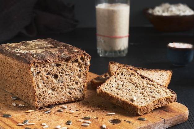 Chleb Na Zakwasie, Pełnoziarnisty Chleb żytni Z Pestkami Dyni I Słonecznika. Zakwas Na Stole. Autentyczny Domowy Chleb Na Zakwasie - Ekologiczny Produkt Ekologiczny. Produkt Rękodzieła, Kromki Chleba Na Pokładzie Premium Zdjęcia
