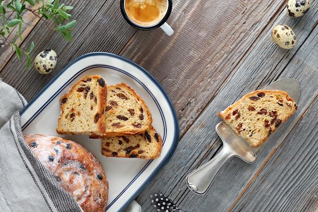 Chleb Wielkanocny (osterbrot Po Niemiecku). Odgórny Widok Tradycyjny Owocowy Chleb Na Nieociosanym Drewnie Z świeżymi Liśćmi I Przepiórek Jajkami Premium Zdjęcia