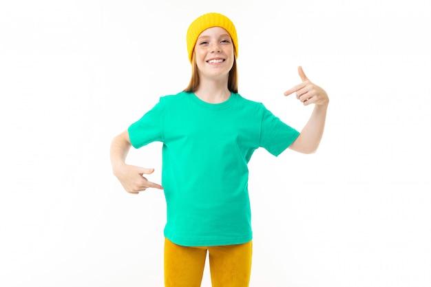 Chłodno Nastolatek Dziewczyna Z Czerwonym Włosy, Błękitną Koszulką I żółtym Kapeluszem Odizolowywającymi Na Białym Tle Premium Zdjęcia