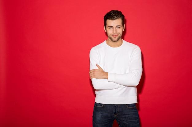 Chłodno Uśmiechnięty Mężczyzna Patrzeje Z Skrzyżowanymi Rękami Nad Czerwieni ścianą W Pulowerze Darmowe Zdjęcia