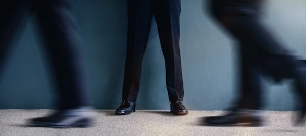 Chłodny biznesmen stojący przy ścianie w pewnej pozycji. Premium Zdjęcia