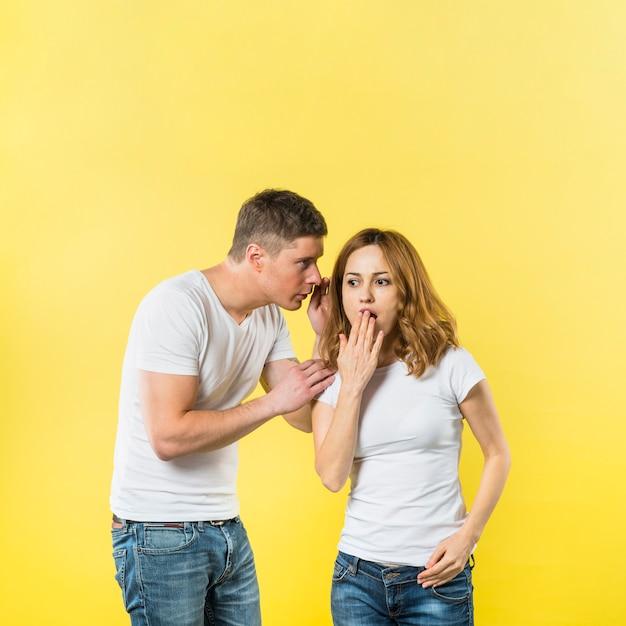 Chłopak Mówi Zaskakującego Sekret Jego Dziewczyna Ucho Przeciw żółtemu Tłu Darmowe Zdjęcia