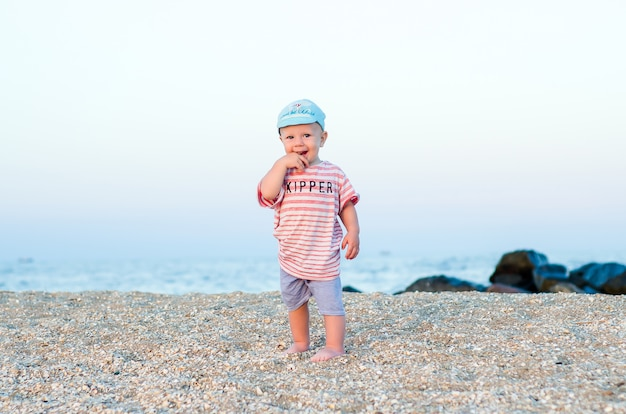 Chłopca Na Piasku W Pobliżu Morza W Niebieskim Kapeluszu I Paski Ubrania. Koncepcja Lato. Wakacje Relaksujące, Wakacje Na Plaży. Premium Zdjęcia