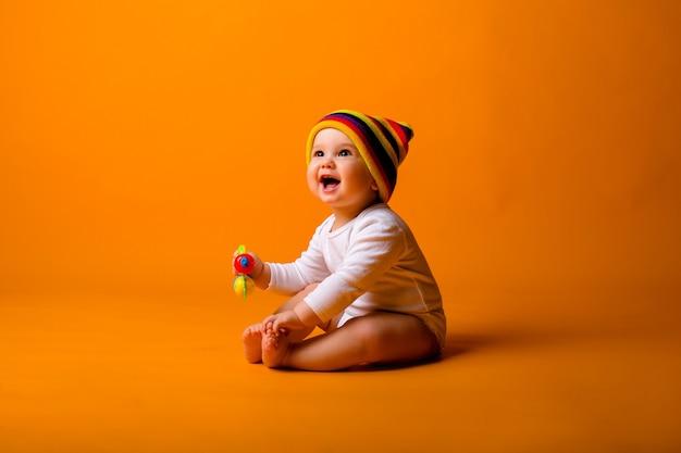 Chłopca W Białym Body I Wielobarwny Kapelusz Trzyma Zabawkę, Siedząc Na Pomarańczowej ścianie Premium Zdjęcia