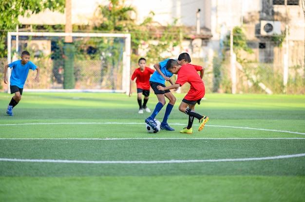 Chłopcy grający w piłkę nożną na boisku treningowym Premium Zdjęcia
