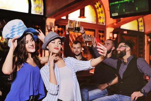 Chłopcy I Dziewczęta W Bawarskich Kapeluszach Piją Piwo Premium Zdjęcia
