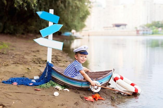 Chłopczyk Siedzi W łodzi, Przebrany Za Marynarza Na Piaszczystej Plaży Z Muszelkami Nad Morzem Premium Zdjęcia