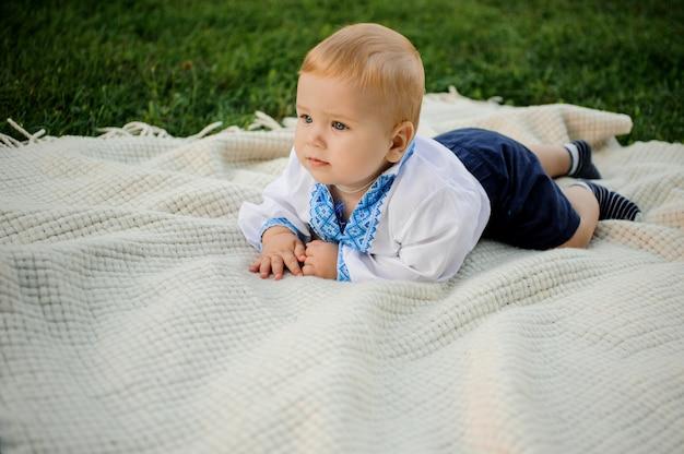 Chłopczyk ubrany w haftowaną koszulę leżącą na szkockiej kracie na zielonej trawie Premium Zdjęcia