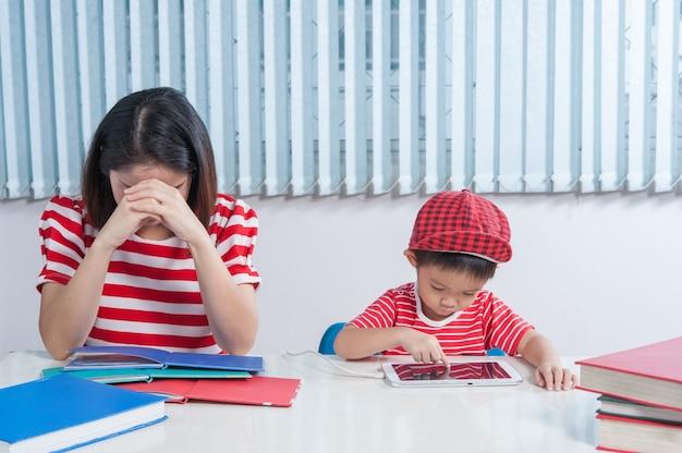 Chłopiec Azjatyckich Odtwarzanie Tabletu I Jego Matka Sfrustrowany. Darmowe Zdjęcia