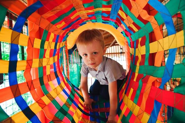 Chłopiec Bawi Się Na Placu Zabaw, W Labiryncie Dla Dzieci Premium Zdjęcia