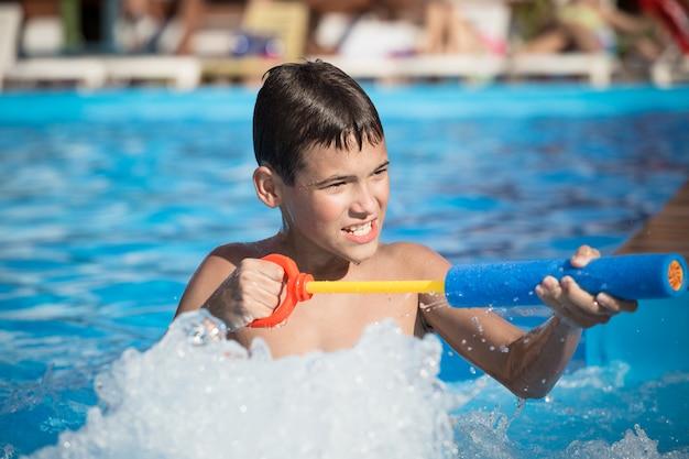 Chłopiec Bawi Się W Basenie Z Pistoletem Na Wodę Premium Zdjęcia