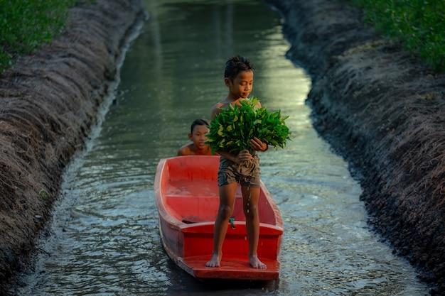 Chłopiec Bawić Się W Warzywa Uprawia Ziemię Blisko Damnoen Saduak Pływającego Rynku, Ratchaburi Prowincja Premium Zdjęcia