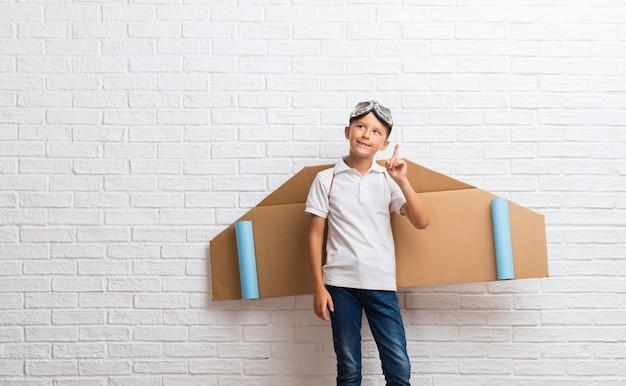 Chłopiec Bawić Się Z Kartonowymi Samolotowymi Skrzydłami Na Jego Plecy Stoi I Myśleć Pomysł Premium Zdjęcia