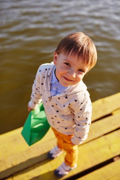 Chłopiec bawić się z zabawkarskim papierowym statkiem jeziorem Darmowe Zdjęcia