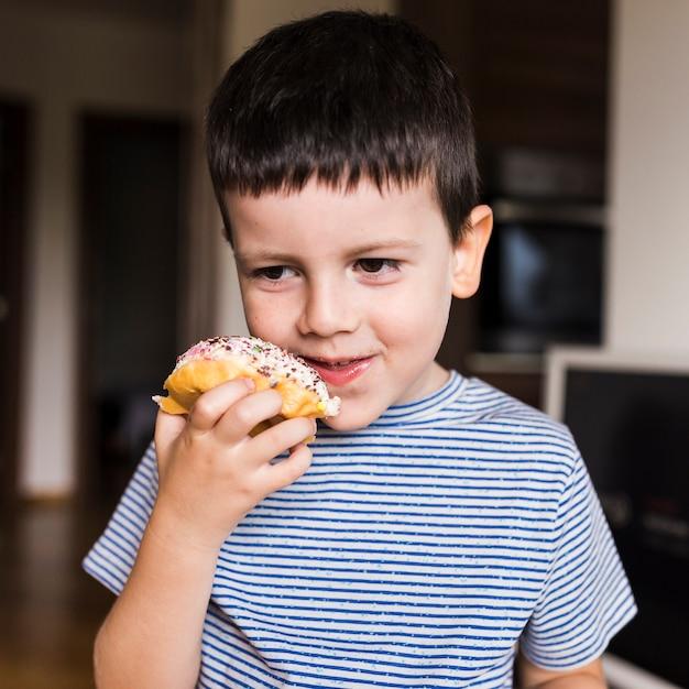 Chłopiec cieszy się doughnout w domu Darmowe Zdjęcia