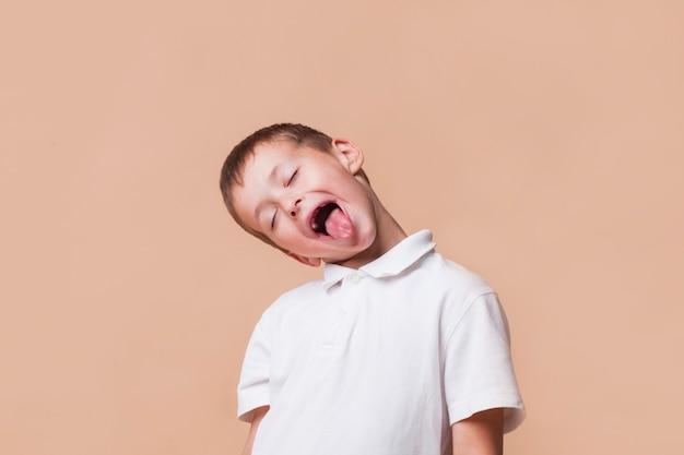 Chłopiec dokucza z zamkniętym okiem na beżowym tle Darmowe Zdjęcia