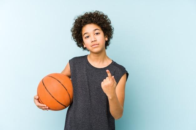 Chłopiec Dziecko Gra W Koszykówkę Na Białym Tle Na Niebieskiej Przestrzeni, Wskazując Palcem Na Ciebie, Jakby Zapraszając Podejść Bliżej. Premium Zdjęcia