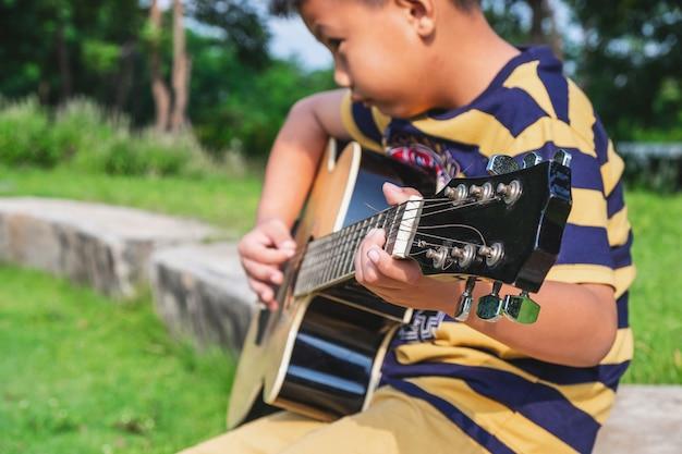 Chłopiec gra na gitarze w ogrodzie. Premium Zdjęcia